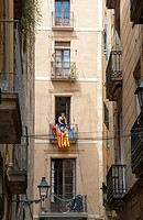 young woman hanging laundry on her balcony draped with Catalan flag in the Gothic Quarter of Barcelona, Catalonia, Spain.