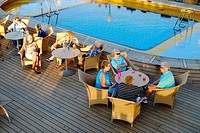 Senior couples relax on the deck of a cruise ship.