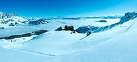 Cloudy winter mountain panorama. Ski resort. All people are not recognizable.