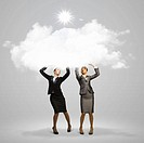 Image of two businesswomen holding clouds above head