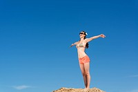 beautiful young woman standing on a background of blue sky with open arms