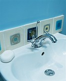 Close-up of wall tiles above chrome tap and white basin