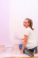 Girl paints house in lilac color