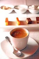 Cup of coffee and sweets on table