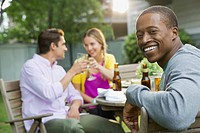 Portrait of happy man with friends at outdoor dining table