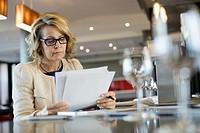Businesswoman reading document in hotel restaurant