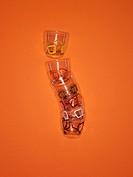 Stack of colourful squares designed glasses on orange background