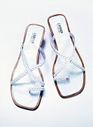 Pair of white flip-flops on white background