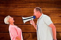 Composite image of man shouting at his partner through megaphone