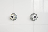 Taps on tiled wall