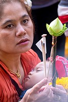 Asia. Thailand, Chiang Mai. Woman with her baby praying at temple.