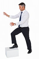 Businessman with one foot on a cube and arms out