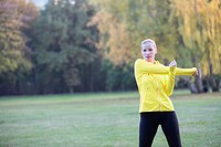 Young blonde woman doing gymnastics in park
