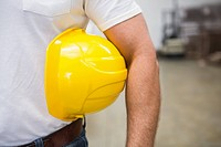 Close up of warehouse worker holding a hard hat