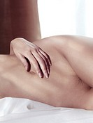 Artistic closeup of a nude woman body lying in bed.