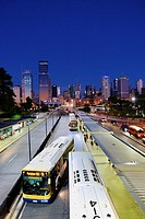 people and buses at South Bank bus stop with Brisbane city skyline at dusk.