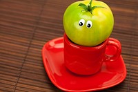 tomato with eyes in the cup on a bamboo mat