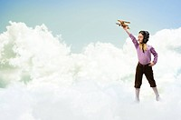 girl in helmet pilot playing with a toy wooden airplane in the clouds, dreaming of becoming a pilot