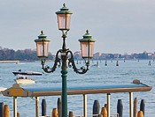 Old fashioned decorative street lamp next to a water taxi stop on Venice Lagoon, Veneto, Italy, Europe.