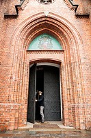 Man exits the arched doorway of the Gothic Revival styled St. Florian Cathedral, Praga district, Warsaw, Poland, Central Europe.