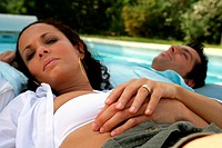 Couple lying by a pool