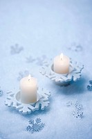 two candles with a Christmas setting
