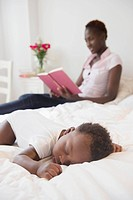 Black mother reading near sleeping baby boy
