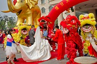 China, Shandong, Yantai. A newly married couple go through the motions of their colorful wedding celebration.