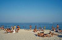 People sunbathing on sandy beach beside the Black Sea.