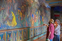 Ocotlán de Morelos, Oaxaca, Mexico - Tourists study a mural by Mexican painter Rodolfo Morales at the Municipal Palace of Ocotlán.