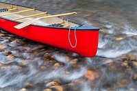 red canoe bow with a rope and paddle against a shallow river rapid