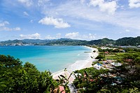 Gentle waves of the aquamarine sea breaking on the two mile stretch of the white sand Grand Anse Beach with the capital city of St George's in the dis...