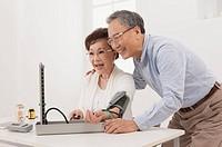 Senior woman measuring and smiling with senior man