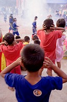 Thai boys cover their ears watching firecrackers exploding at local temple.