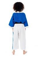 School girl in karate uniform facing wall, rear view