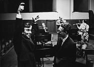 Italian conductor Claudio Abbado raising his arms while talking to Italian pianist Maurizio Pollini all'interno di un teatro. Florence (Italy), 1966