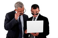 businessmen wearing sunglasses looking at a laptop