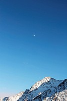 Winter alpine mountains covered with snow and moon