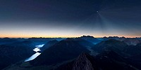 sunrise in mountains of austrian alps with moonlight and reflecting lake
