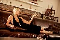 Young woman in evening gown having a cognac, Dubrovnik, Croatia
