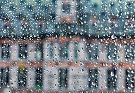 Medieval building visible through glass covered by rain drops