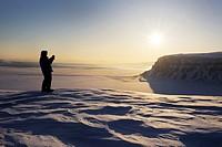 Expedition member looking over the frozen Tempelfjorden at sunset, Spitsbergen (Svalbard).
