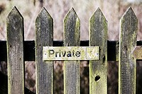 Weathered wooden gate with private sign.