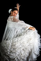 Flamenco dancer backs with white dress and hands crossed up on black background.