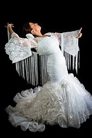 Flamenco dancer dressed in white with expression of feeling passionate in black background.