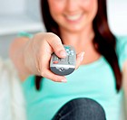 Close-up of a smiling woman hoding a remote in the living-room
