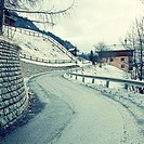 Curved country road in winter Alps