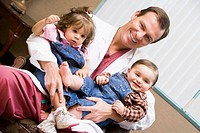 Doctor sitting with two IVF children smiling