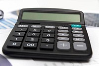 Businessman analyzing investment charts with calculator and lapt