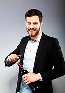 Handsome man opening bottle of wine